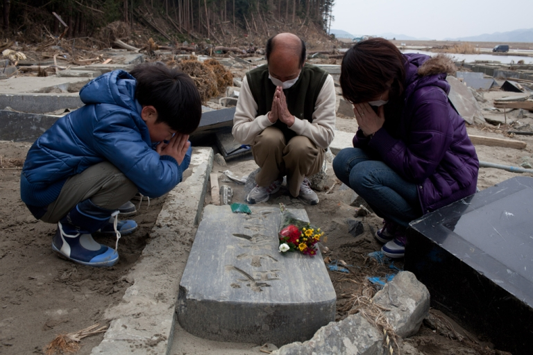 <p>A month after the tsunami devastation, a family prays by a grave in Ishinomaki, Miyagi prefecture on April 11, 2011.</p>
