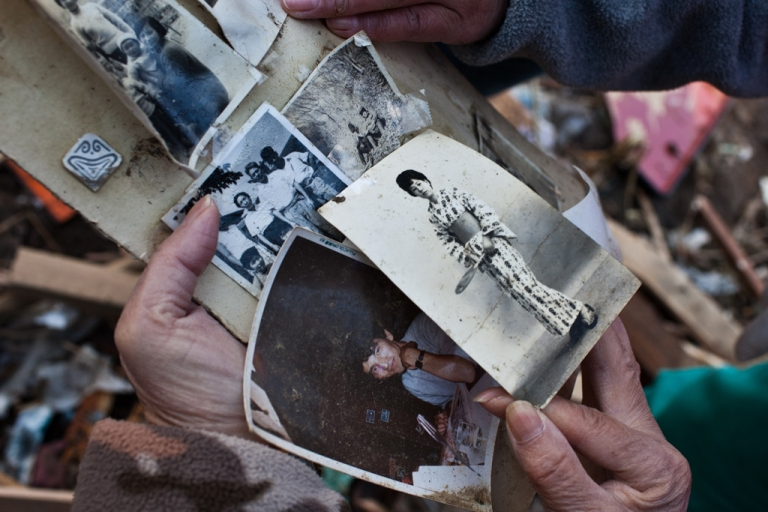 <p>A family member retrieves photographs of her missing grand father and mother's old photos amongst debris in Minamisanriku, Miyagi prefecture, March 28, 2011.</p>
