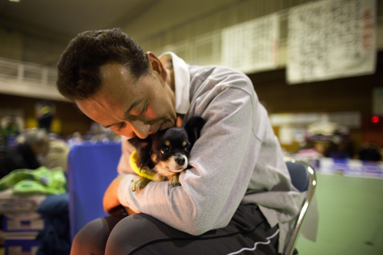 <p>A man hugs his dog to keep it warm as earthquake victims pack an evacuation center March 20, 2011 in Ofunato, Japan. More than a week after the magnitude 9.0 earthquake and tsunami struck Japan, the death toll has risen to over 8,000 with thousands more still missing.</p>