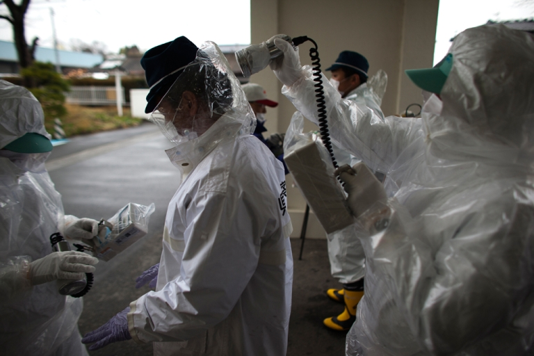 <p>Japanese policemen wearing a protective suits undergo testing for possible nuclear radiation at screening center about 35 kilometers away from Fukushima Nuclear Power Plant as they finish their duty inside exclusion zone on April 9, 2011 in Minamisoma, Fukushima Prefecture, Japan</p>