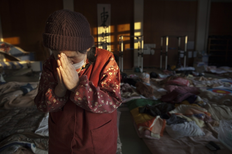 <p>Momoko Onodera, whose husband died in the tsunami, prays at an evacuation center on March 18, 2011 in Kesennuma, Japan.</p>