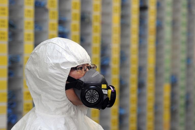 <p>An engineer wears radiation protective gear.</p>