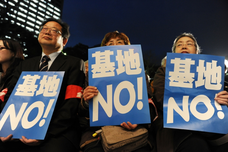 <p>Anti-US military base protesters hold posters reading