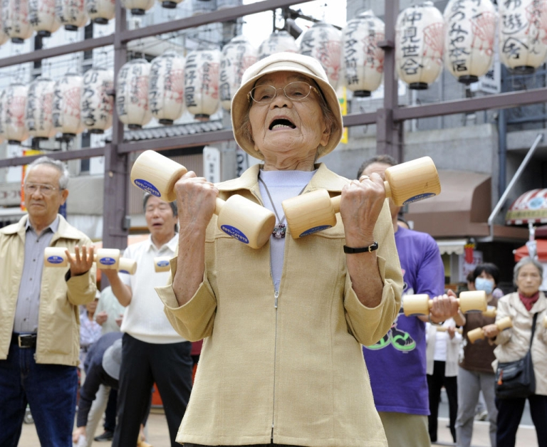 <p>Elderly people work out with wooden dumb-bells in the grounds of a temple in Tokyo.</p>
