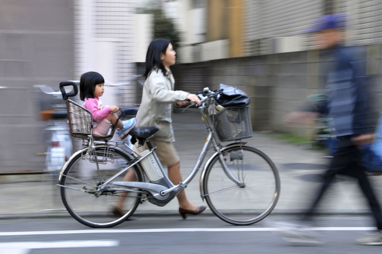 <p>A mother pushes her bicycle carrying her daughter in Tokyo on March 19, 2010.</p>