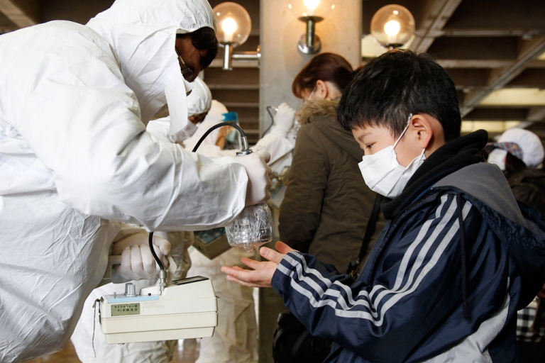 <p>An official in a full radiation protection suit scans an evacuated boy with a geiger counter to check radiation levels in Koriyama city in Fukushima prefecture.</p>