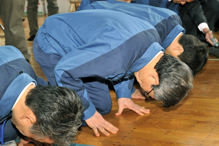<p>Former TEPCO President Masataka Shimizu (center) and company employees bow to apologize to evacuees from the town of Namie near TEPCO's Fukushima nuclear power plant on May 4, 2011.</p>