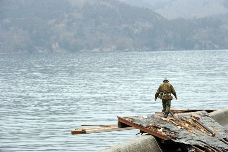 <p>A Japanese Self-Defense Force soldier looks for missing people at a small village beside the Onagawa nuclear plant in Onagawa, Miyagi prefecture, on March 21, 2011.</p>