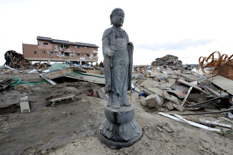 <p>A religious statue stands amongst debris in a tsunami-devastated area close to the sea front, in Natori, Miyagi Prefecture, on March 14, 2011.</p>