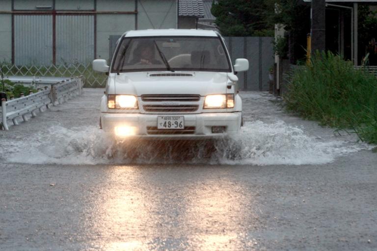 <p>A man drives his car through floodwater triggered by Typhoon Talas at Higashiyama on September 3, 2011 in Himeji, Japan.</p>