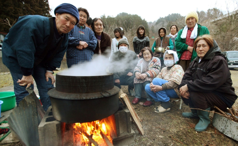 <p>Local residents cook steamed rice at Onagawa town in Miyagi prefecture on March 25, 2011.</p>