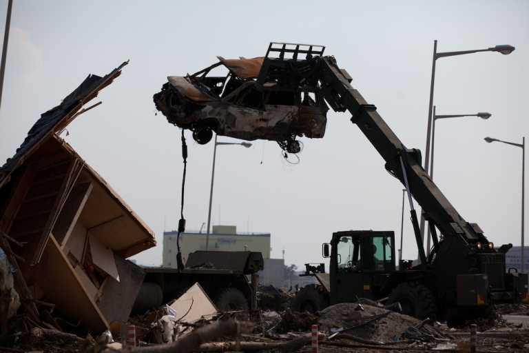 <p>A U.S. military forklift carries a destroyed vehicle at a loading bay platform at Sendai Airport in Miyagi prefecture, Japan, on March 29, 2011.</p>