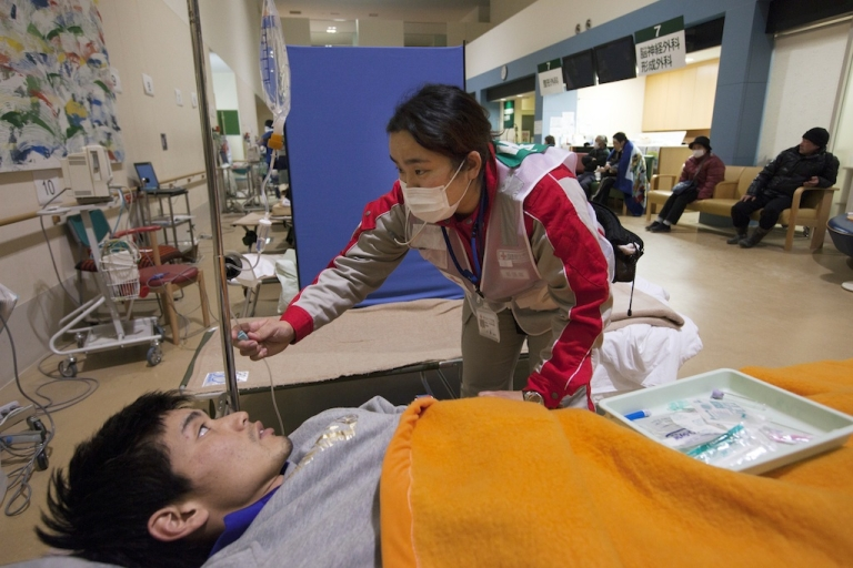 <p>A worker with the Japanese Red Cross takes care of a patient coming from the earthquake shelters at the Ishinomaki hospital March 28, 2011, in Ishinomaki, Japan.</p>