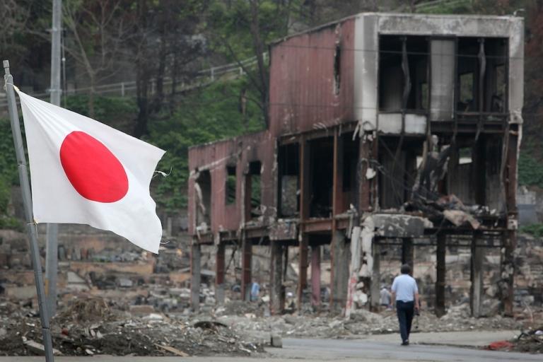 <p>A man walks through debris as the Japanese national flag flies on June 12, 2011, in Otsuchi, Iwate, Japan.</p>