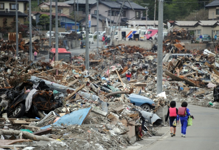 <p>Elementary school students walk beside the rubble after finishing their school in tsunami-devastated town of Otsuchi, Iwate prefecture on May 10, 2011. The debris from the tsunami are projected to hit Hawaiian coast lines by 2013.</p>