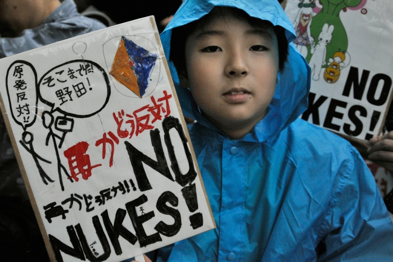 <p>A boy holds a banner denouncing nuclear power plants during a protest in front of the official residence of Japanese Prime Minister Yoshihiko Noda in Tokyo on July 20, 2012.</p>