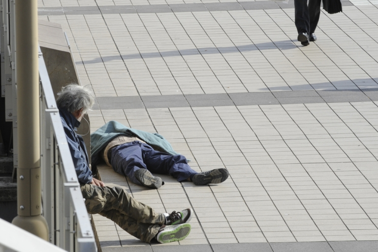 <p>Homeless men sit to receive sunshine along a pedestrian walkway in central Tokyo on November 30, 2010. Unemployment, an aging population and reluctance to ask for welfare assistance might be contributing to a rise in