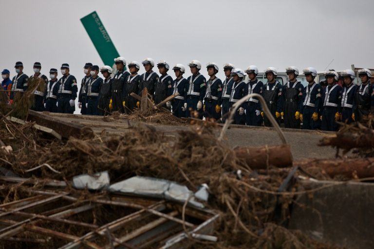 <p>A month after the devastating tsunami, Japanese police officers have a moment of silence at the time of 2:46 when the earthquake hit the country in Ishinomaki, Miyagi prefecture on April 11, 2011. Japan said it was to widen the evacuation area around a crippled nuclear plant to include territory outside the current 12-mile exclusion zone.</p>