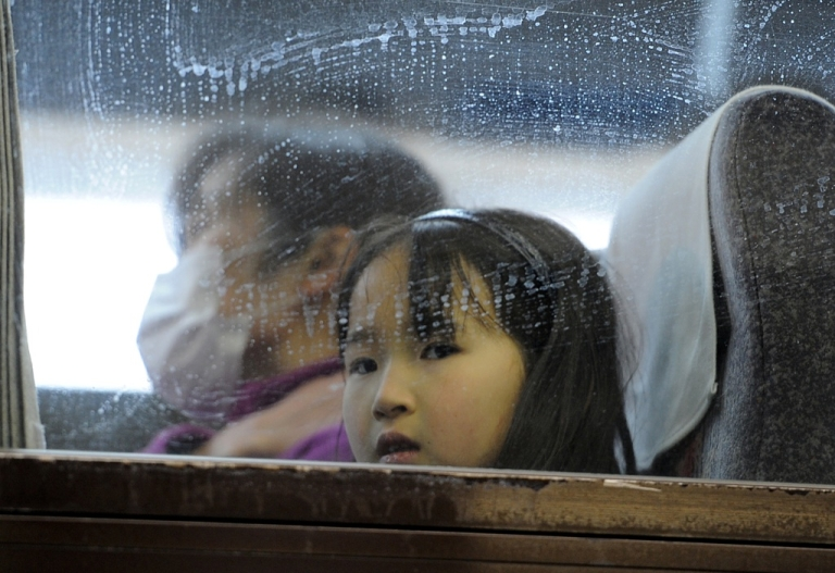 <p>A young girl looks out from a bus window after explosions and a fire at Japan's quake-hit nuclear plant in neighboring Fukushima prefecture unleashed dangerous radiation on March 15.</p>