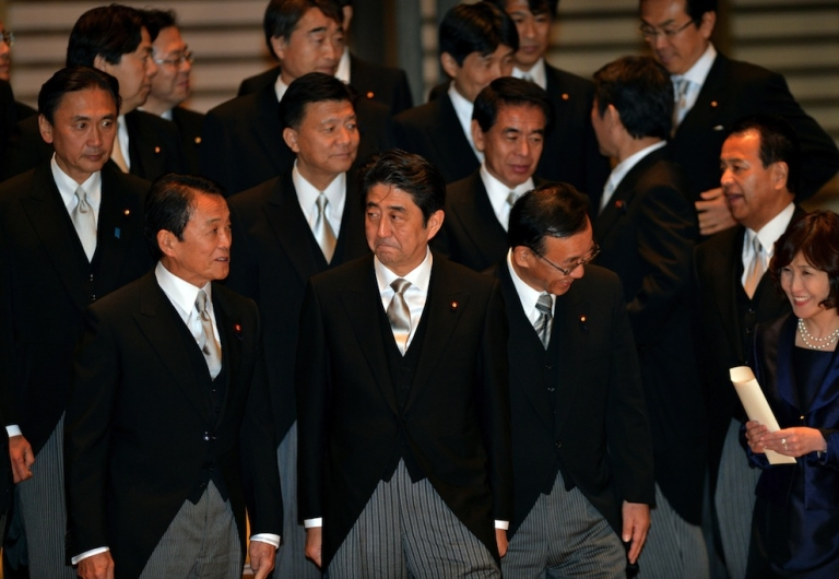<p>Japan's new Prime Minister Shinzo Abe (C), accompanied by Finance Minister Taro Aso (3L) and Justice Minister Sadakazu Tanigaki (2nd R), waits for his vehicle after a photo session with his cabinet members as they were inaugurated before Emperor Akihito at the Imperial Palace in Tokyo on December 26, 2012. Abe was elected Japan's prime minister by the lower house of parliament after he swept to power on a hawkish platform of getting tough on diplomatic issues while fixing the economy.</p>