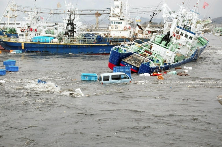 <p>Fishing boats and vehicles are carried by a tsunami wave at Onahama port in Iwaki city, in Fukushima prefecture, northern Japan on March 11, 2011.</p>