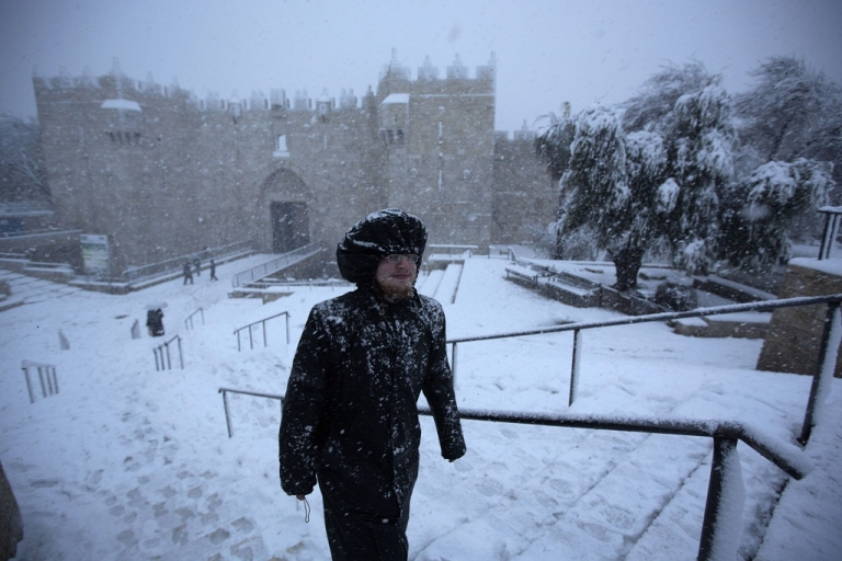 <p>An ultra-orthodox Jewish man runs as snow falls next to Damascus gate in the old city of Jerusalem on January 10, 2013.</p>