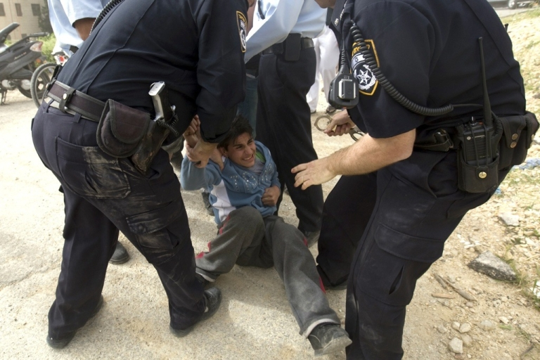 <p>Israeli police arrest a young member of Khaled Natshe's family as they are forced to hand over their home to Jewish settlers in the Israeli annexed east Jerusalem neighborhood of Beit Hanina, on April 18, 2012.</p>