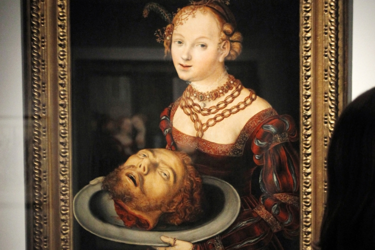 <p>A woman looks at a painting entitled