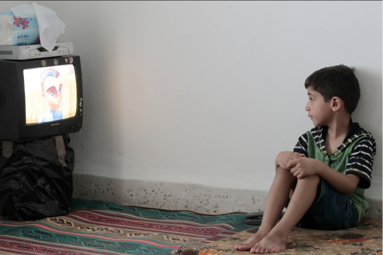 <p>A Syrian refugee child watches television at a house in Amman, Jordan, on May 30, 2012. Tens of thousands of Syrian refugees who have fled from carnage and violence at home to neighbouring Jordan are draining the desert kingdom's meagre water resources, officials and experts say.</p>
