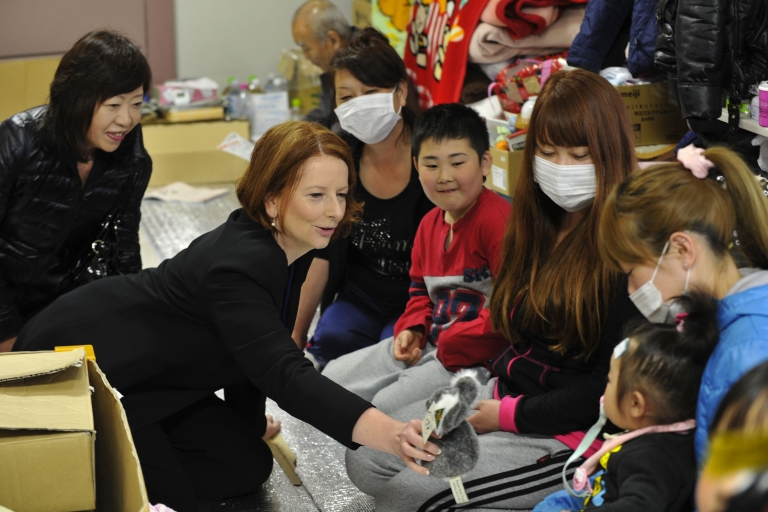 <p>Australian Prime Minister Julia Gillard (C) presents a toy koala to a child during a visit to a tsunami survivor's shelter in the town of Minamisanriku, Miyagi prefecture on April 23, 2011.</p>