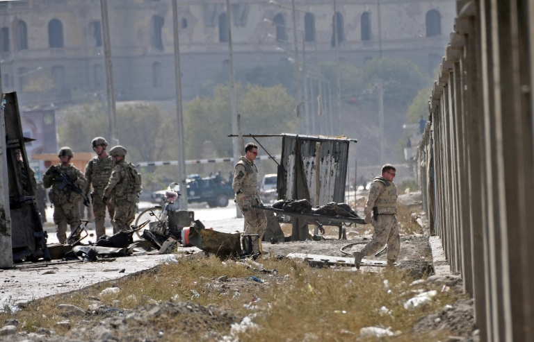<p>NATO forces carry a corpse from the site of a suicide attack near Darul Aman Palace in Kabul on October 29, 2011.</p>