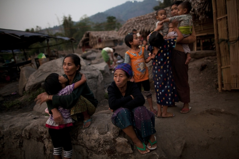 <p>Displaced Kachin villagers sit and stand near temporary huts at the Wai Shyai IDP camp in Laiza, Kachin state, Burma, March 29, 2012. Around 2,423 people are currently living at the camp, which was established in June of 2011.</p>