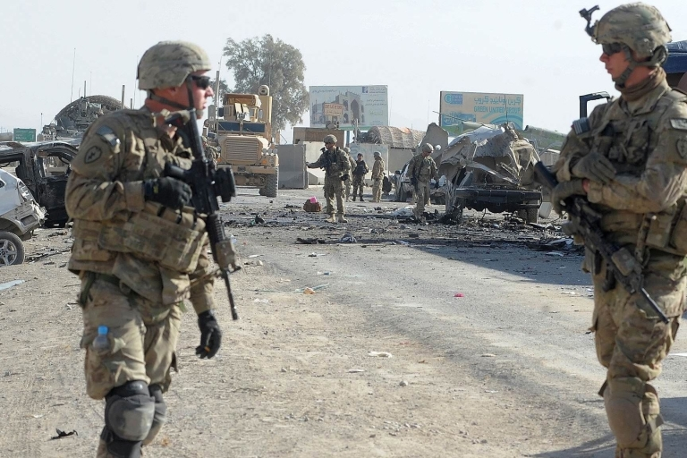 <p>US soldiers inspect the site of a suicide attack near the entrance to Kandahar international airport on January 19, 2012.</p>