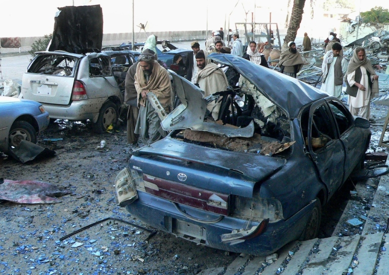 <p>Afghan bystanders inspect damaged vehicles at the site of an attack by suicide bombers in Kandahar on February 15, 2011.</p>