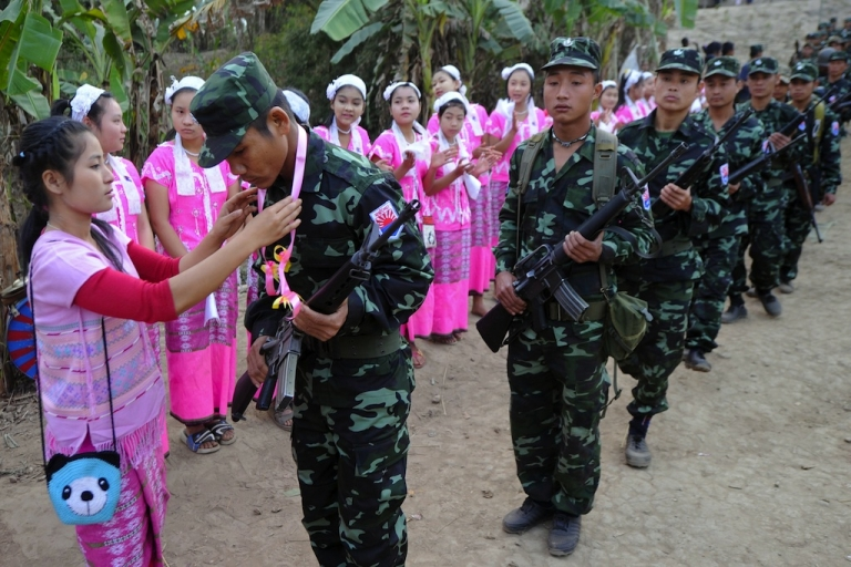 <p>Karen women (L) dressed in traditonal clothing present garlands to Karen National Union (KNU) soldiers during the celebration of 63rd anniversary of the Karen Revolution day in Karen State, near the Thai-Myanmar border on January 31, 2012.</p>