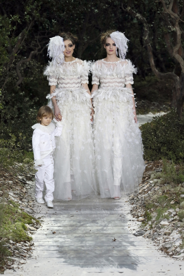 <p>Models present creations for Chanel with Hudson Kroenig, German designer Karl Lagerfeld's godson, during the Haute Couture Spring-Summer 2013 collection shows on Jan. 22, 2013 at the Grand Palais in Paris.</p>