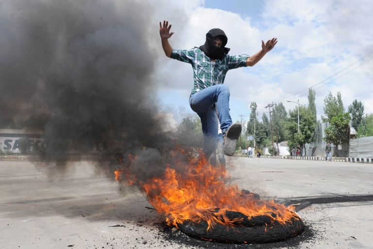 <p>A Kashmiri protester leaps above a burning tire on Sept. 18. He's among a group of angry demonstrators who clashed with Indian police over an anti-Islam film made in the US.</p>