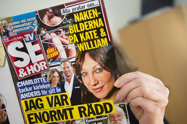 <p>A woman holds a copy of the celebrity magazine Se &amp; Hor in Stockholm on September 20, 2012,  showing Britain's Prince William and a topless Princess Kate taken while on holiday in France on September 5.</p>