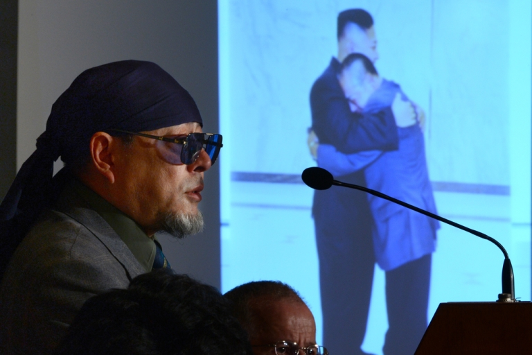 <p>Kenji Fujimoto, former personal chef of late North Korean leader Kim Jong Il, speaks as a projector displays the cover of his book showing Fujimoto hugging North Korean leader Kim Jong Un, in Tokyo on Dec. 6, 2012.</p>
