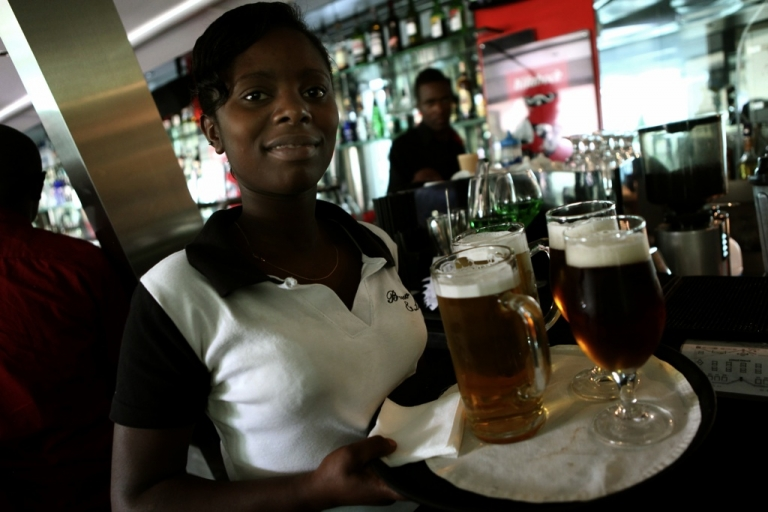 <p>A waitress serves beer in East Africa.</p>