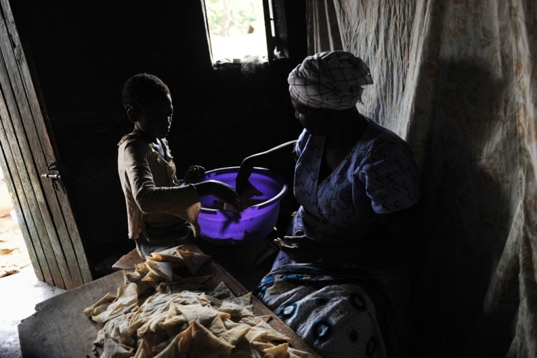 <p>A Kenyan grandmother and her granddaughter prepare a meal.</p>