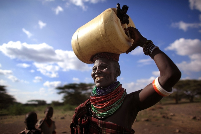 <p>A woman from the remote Turkana tribe in Northern Kenya carries water from a well.</p>