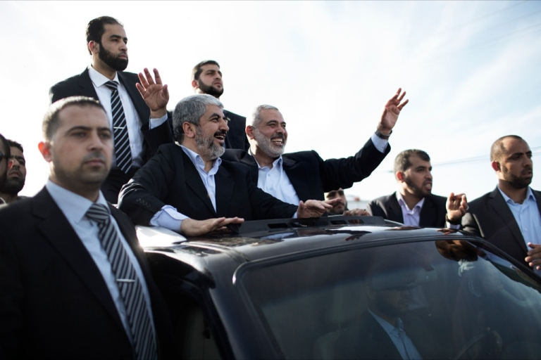 <p>Hamas leader-in-exile Khaled Mashaal (C-L) and Hamas leader in the Gaza Strip Ismail Haniya (C-R) wave from the rooftop of a vehicle during a parade following Meshaal's arrival in Rafah, southern Gaza, on December 7, 2012. Meshaal is making his first-ever visit to the Gaza Strip amid tight security for festivities marking the ruling Islamist movement's 25th anniversary.</p>