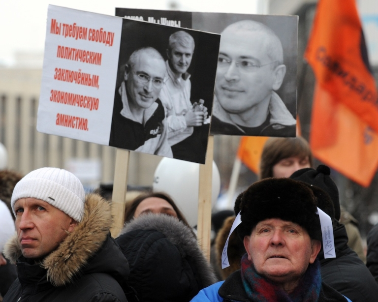 <p>People hold portraits of jailed oil magnate Mikhail Khodorkovsky as they protest against the December 4 parliament elections in Moscow, on December 24, 2011.</p>