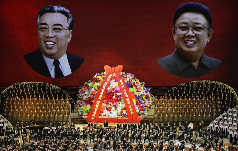 <p>North Korean performers sing in front of portraits of founding president Kim Il-sung (L) and his son Kim Jong-il during celebrations to mark the 100th anniversary of the birth of Kim Il-sung in Pyongyang on April 16, 2012.</p>