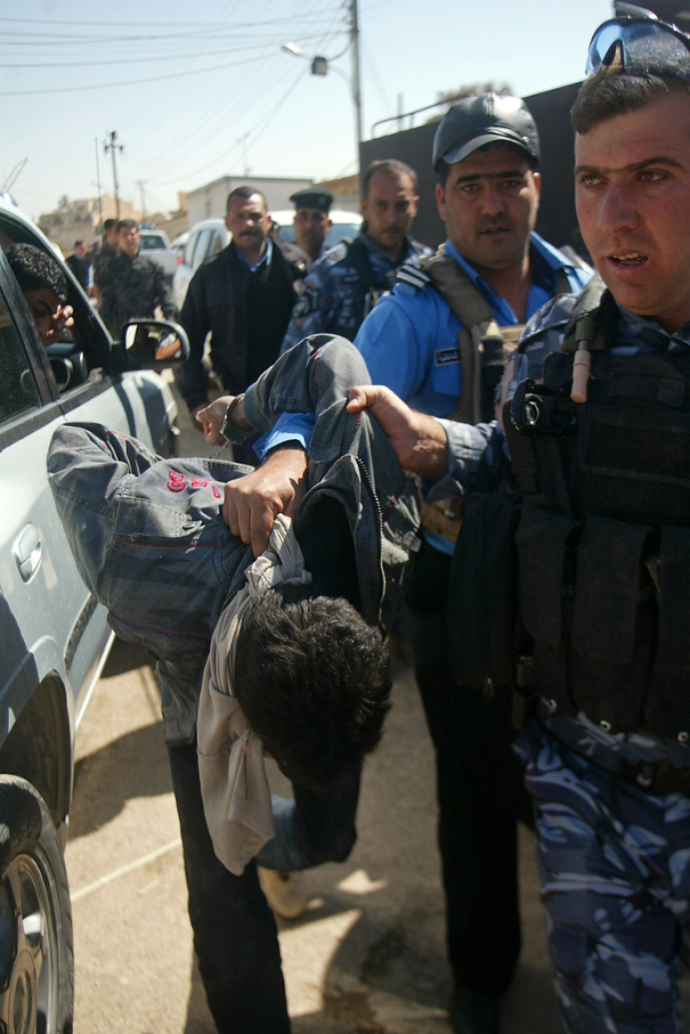<p>Iraqi policemen drag a man suspected of being among 19 detainees who escaped from a prison in the northern Iraqi city of Kirkuk on March 23, 2012.</p>