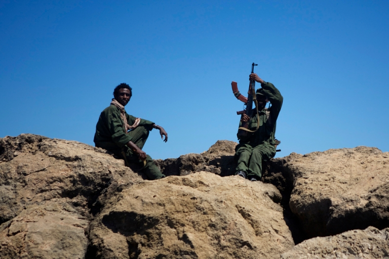 <p>Two Ras Kamboni Brigades fighters rest on the sea wall at Kismayo port.</p>