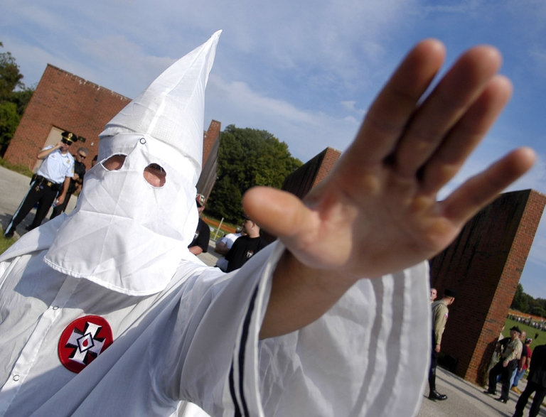 <p>A member of the Ku Klux Klan salutes during an American Nazi Party rally. The KKK in South Carolina recently lost a lawsuit to New Beginnings Baptist Church; the congregation and its reverend have been ruled to be the rightful owners of the Redneck Shop, which sells KKK robes and t-shirts.</p>