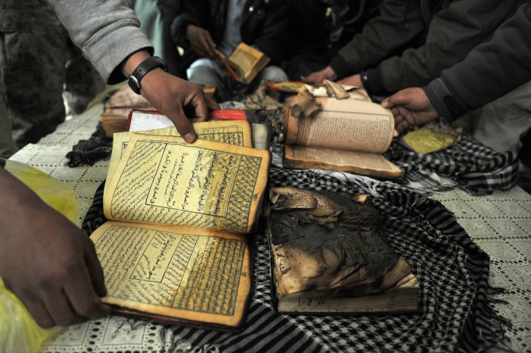 <p>Demonstrators show copies of the Koran allegedly set alight by US soldiers serving with NATO forces in Afghanistan, during a protest at the gate of Bagram airbase on Feb. 21, 2012.</p>