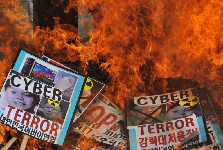 <p>South Korean conservative activists burn placards containing images of North Korean leader Kim Jong-Iland his son Kim Jong-Un during an anti-North Korean rally in Seoul on July 10, 2009. The activists were denouncing the North's cyber attacks and demanding a release of US female journalists detained by the North.</p>